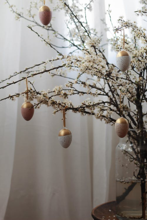Blooming tree twigs decorated with egg shaped baubles