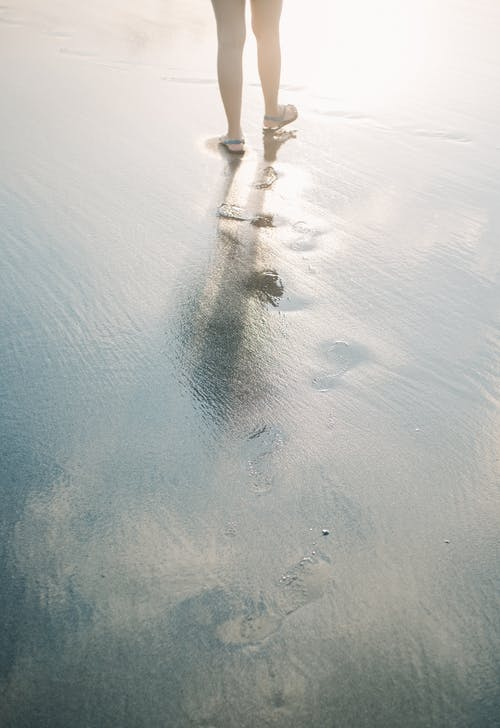Person in White Shirt and Blue Denim Jeans Walking on Wet Sand