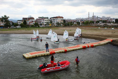 Group of sportsmen in sailboats floating by coast