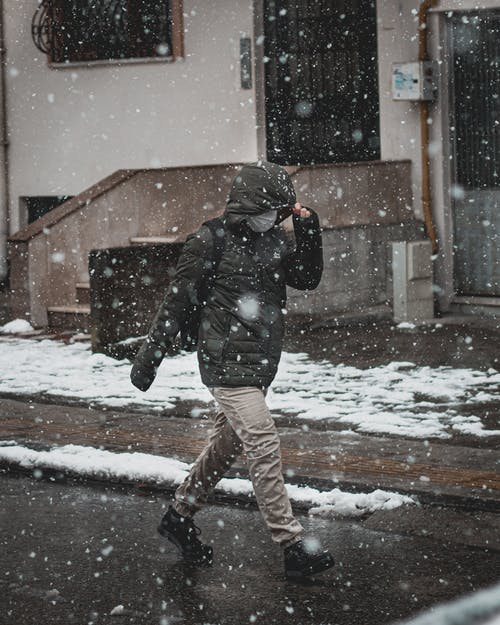Full body of anonymous male in warm jacket and protective mask walking down street with residential buildings in snowfall