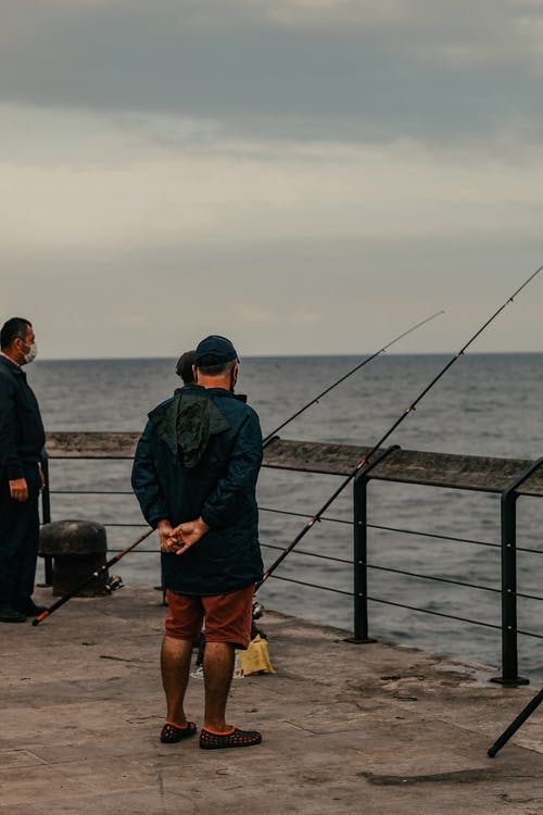 Unrecognizable man standing near fishing rods