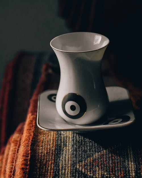 Porcelain cup of hot aromatic coffee on white saucer placed on colorful vintage carpet on daylight