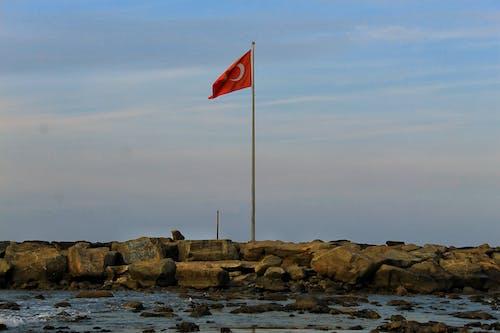 Turkish Flag waving over stones near sea