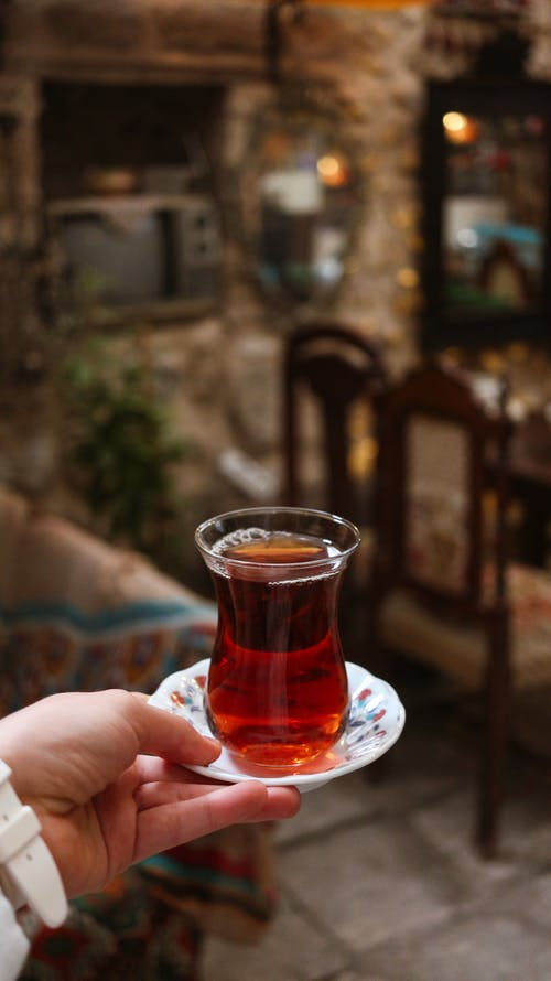 Crop person with Turkish glass of tea at home