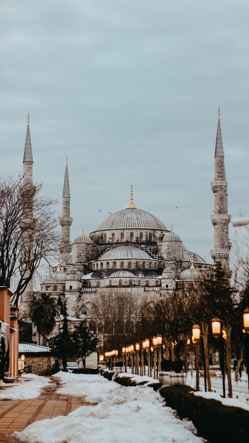 Sultan Ahmed Mosque exterior with towers against snowy walkway and lanterns under cloudy sky in Istanbul Turkey