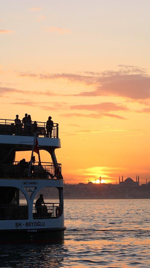 Unrecognizable passengers on ferry sailing on strait under sunset sky