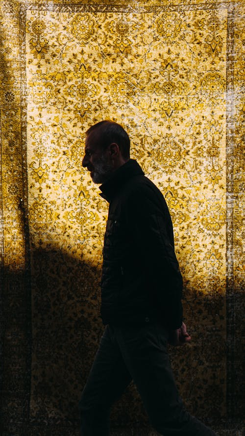 Side view of mature male with hand behind back strolling against rug with oriental pattern and shade on night street