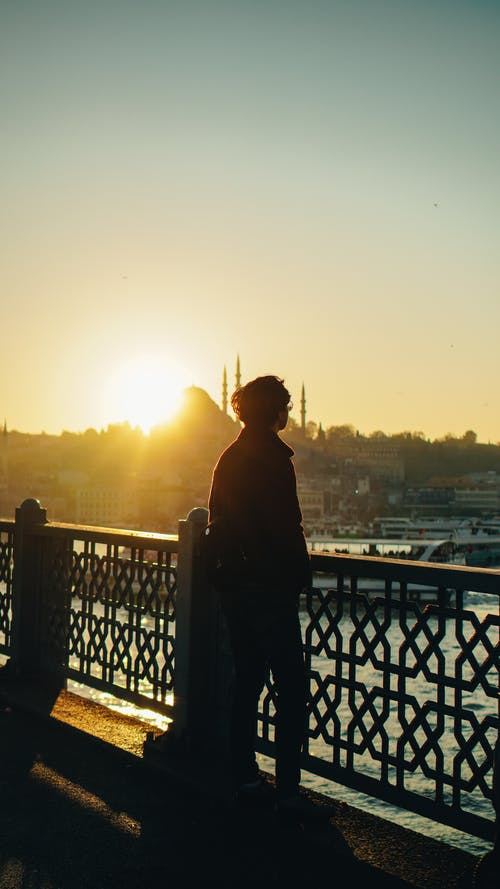 Unrecognizable man contemplating sunset from urban embankment against port