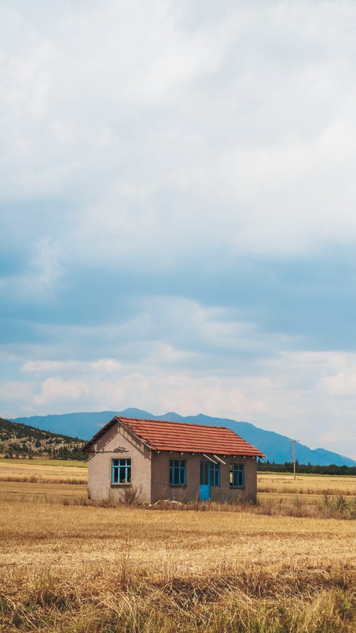 Scenic view of old building facade on meadow against mounts under sky with fluffy clouds in countryside