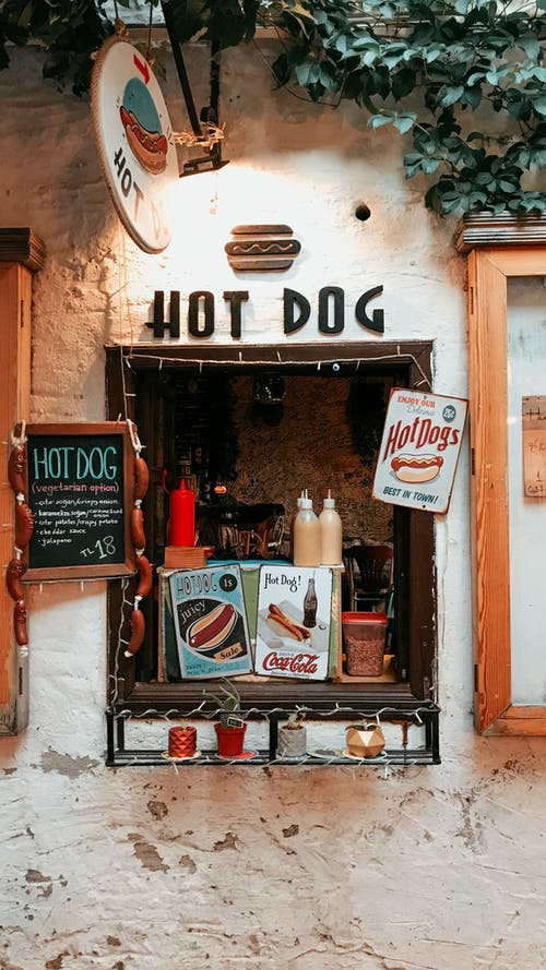 Signboard of takeaway street cafe selling hot dogs with various sauces and drinks