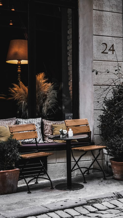 Soft cushions placed near window and round table with chair in veranda of cafe