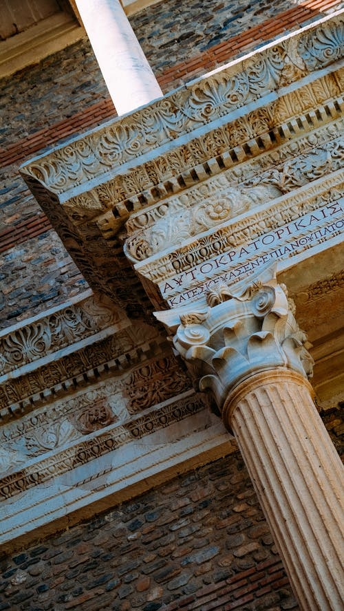 From below of aged stone construction with old decorated columns with ornamental elements and inscription