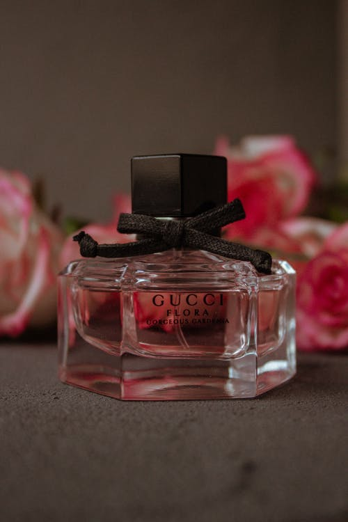 Minimalist transparent bottle of perfume placed on table with bunch of pink flowers against brown background