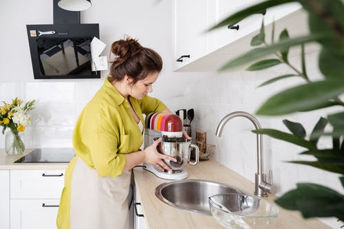 Side view of housewife in apron standing in kitchen and using food processor near sink