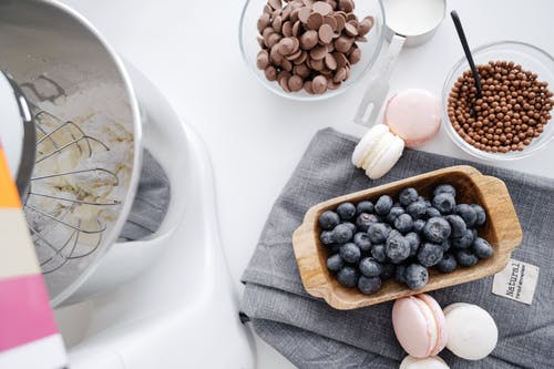 From above composition planetary mixer macaroons wooden bowl with blueberry and chocolate disks for melting