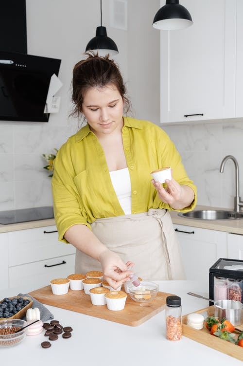 Woman preparing muffins for filling and decorating