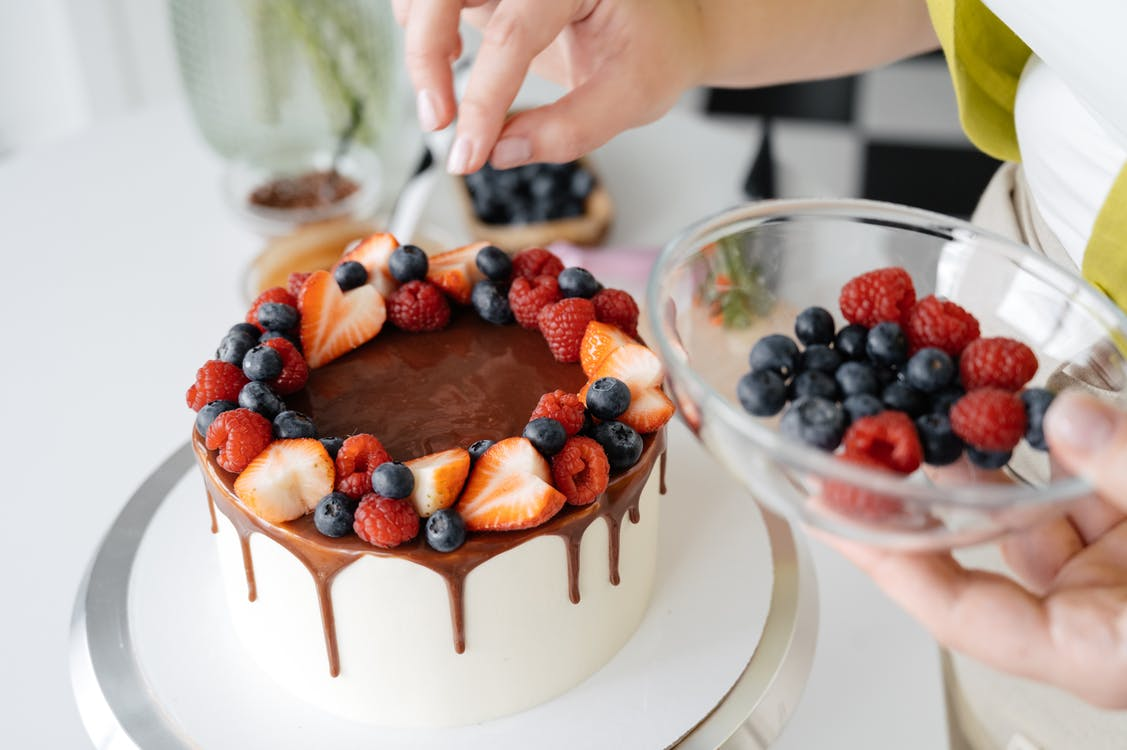 Female confectioner decorating homemade cake with berries