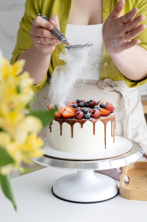 Woman Sprinkling Icing Sugar on Cake with Berries