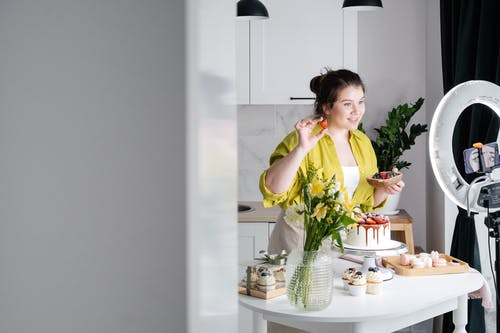 Delighted young female influencer in casual clothes smiling and demonstrating fresh berries while decorating appetizing cake during recording vlog on smartphone in kitchen