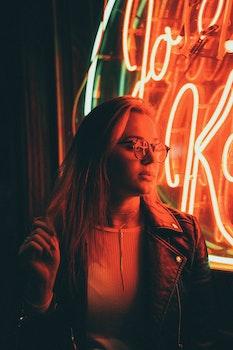 Woman in Denim Jacket Near Neon Signage