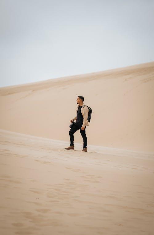 Woman in Black Jacket Walking on Desert