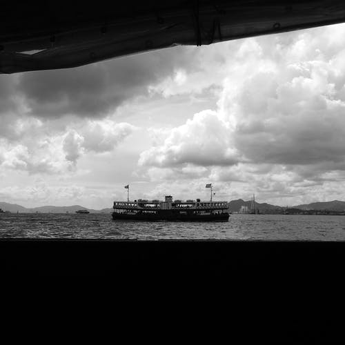 Ship floating under cloudy sky