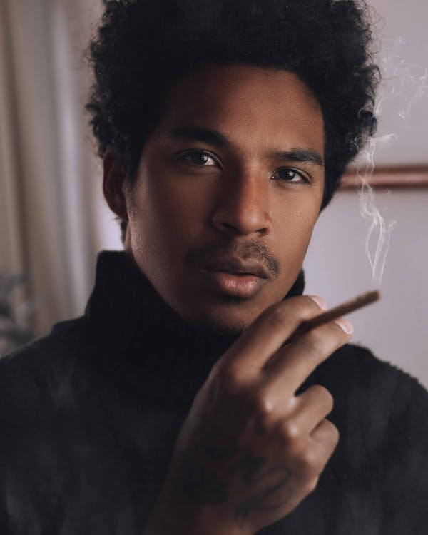 Crop pensive African American male with curly dark hair and mustache smoking cigarette and looking at camera in room
