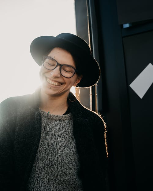 Content young female in warm clothes and glasses with piercing and closed eyes on street in back lit