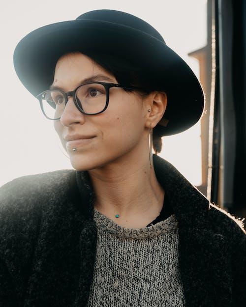 Dreamy woman in eyewear and hat in sunshine