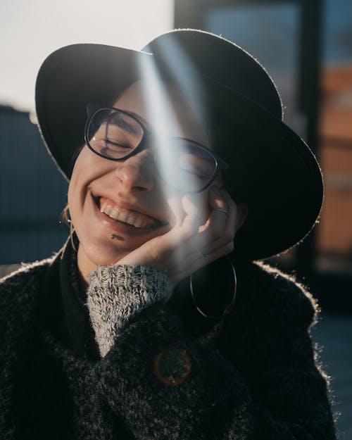 Smiling woman in eyewear and hat in sunbeams