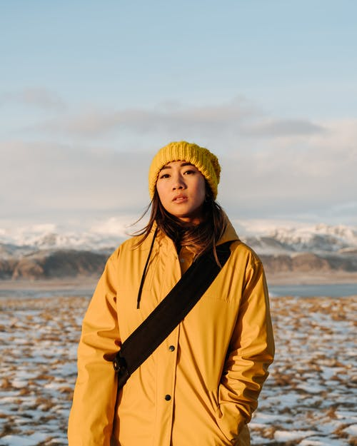 Woman Wearing Yellow Jacket and Beanie Standing in Snow