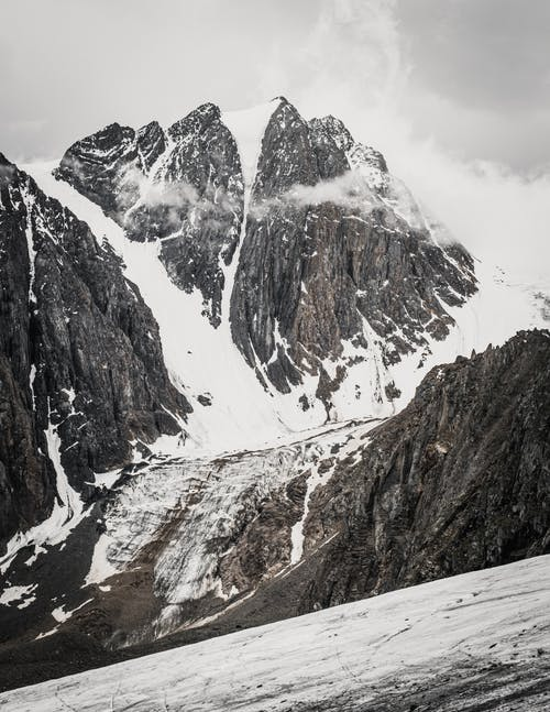 Scenic view of rugged mount with snow and icy waterfall under cloudy sky in misty weather