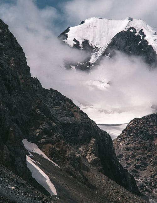 Scenic view of high rough mounts with snow under cloudy sky on sunny day in misty weather
