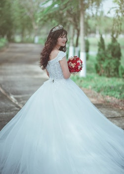 Woman in White Wedding Dress Holding Red Bouquet