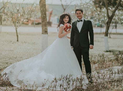 Man and woman wearing wedding dress and suit in between of rice woman wearing white wedding ball beside man wearing black notch lapel suit on pathway near junglespirit Image collections