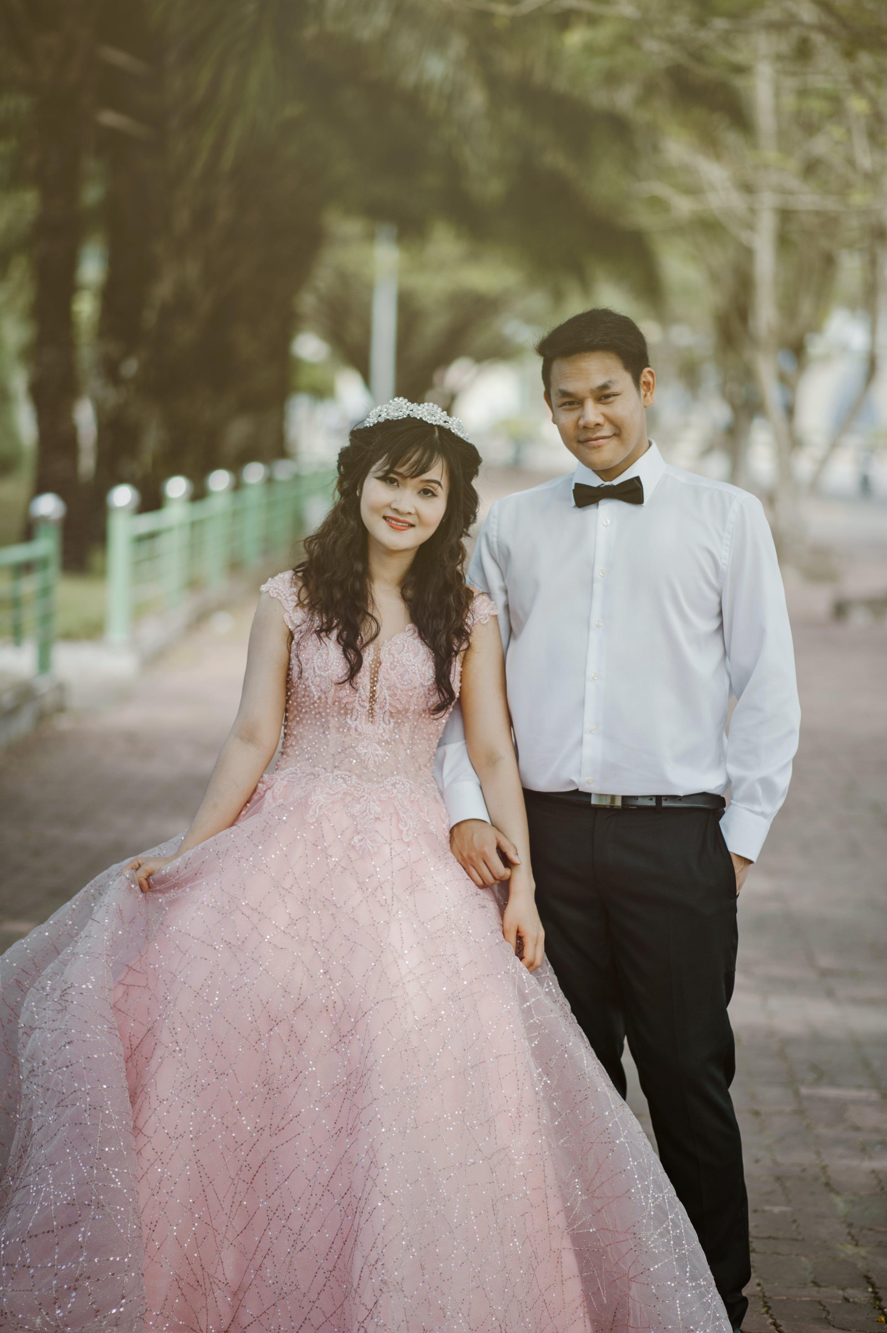 Woman Wearing Pink Wedding Gown Standing Next to Man Wearing White Dress Shirt