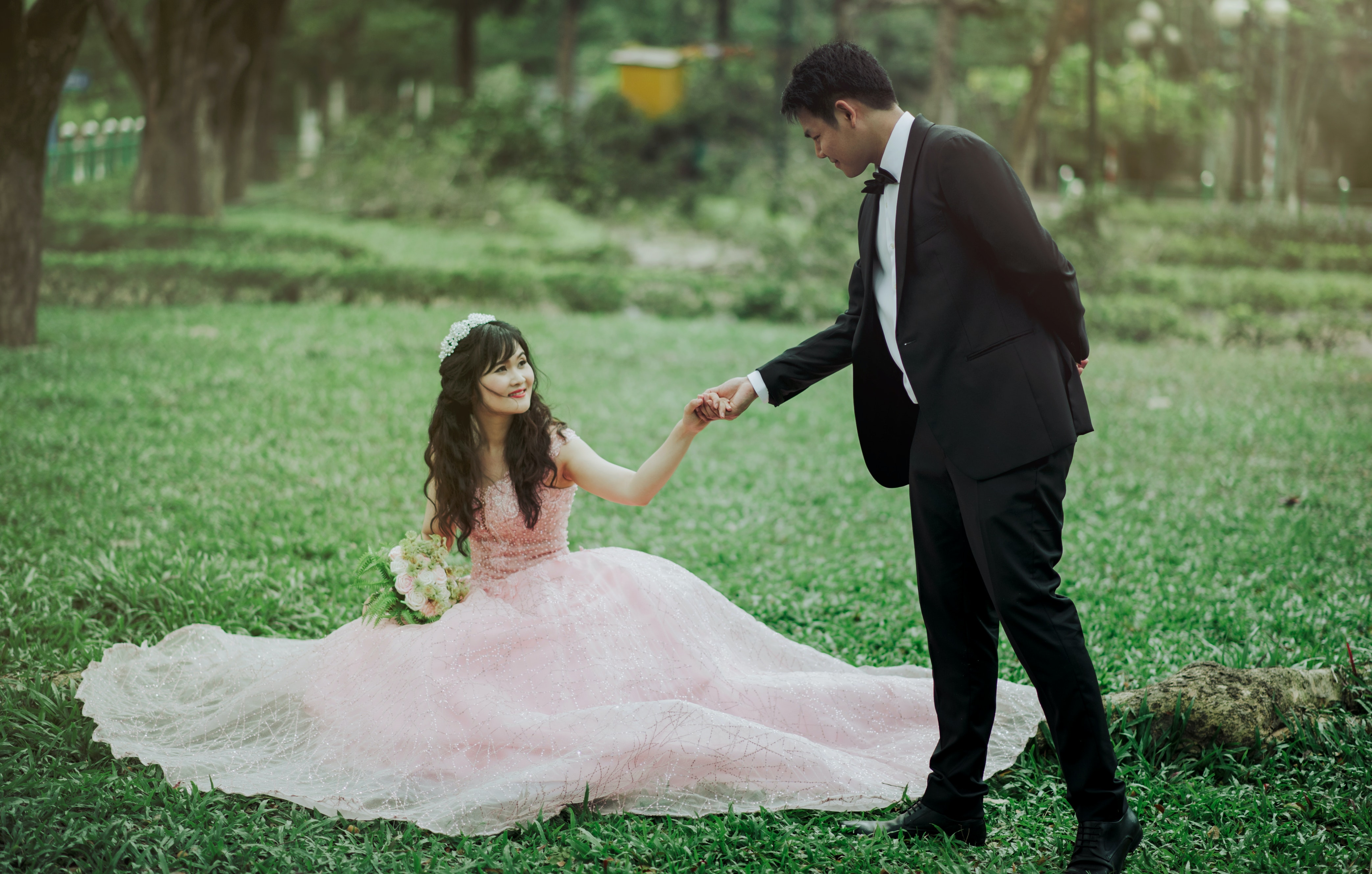 Man in 2-piece Suit Holding Woman in Peach-colored Wedding Gown White Holding Her Flower Bouquet ...