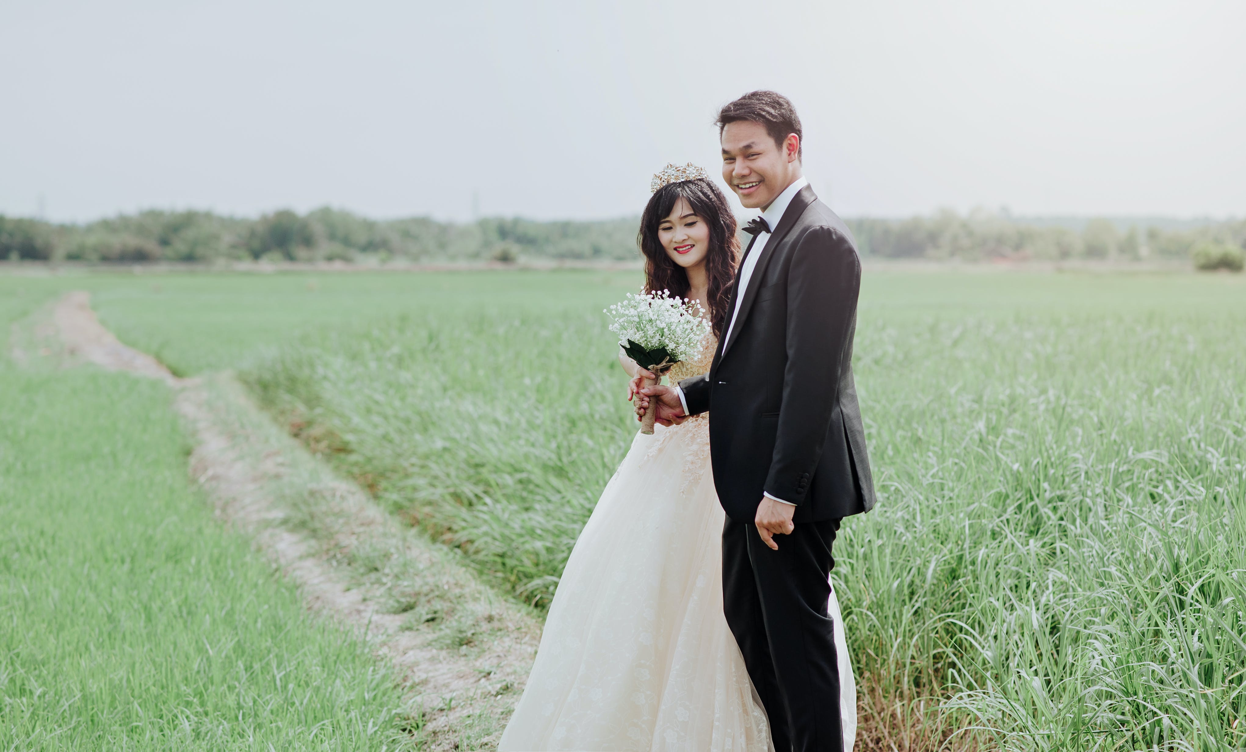 Man and Woman Wearing Wedding Dress and Suit in Between of Rice Fields