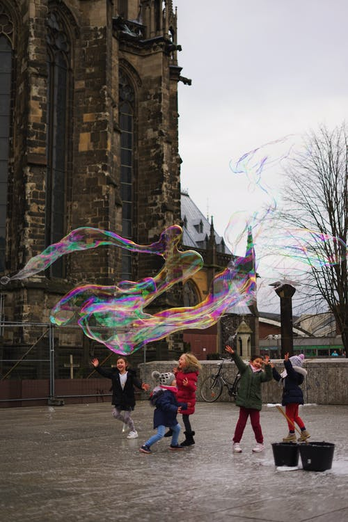 Excited children playing with soap bubbles