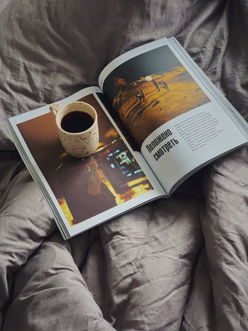 From above cup of aromatic coffee placed on opened magazine on soft cozy bed in morning