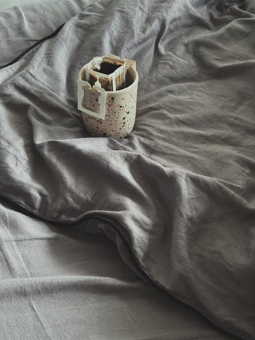 From above cup of aromatic freshly brewed drip coffee with paper filter placed on comfortable soft bed in morning