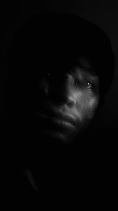 Black and white portrait of thoughtful young Indian male with shadow on face looking away against black background