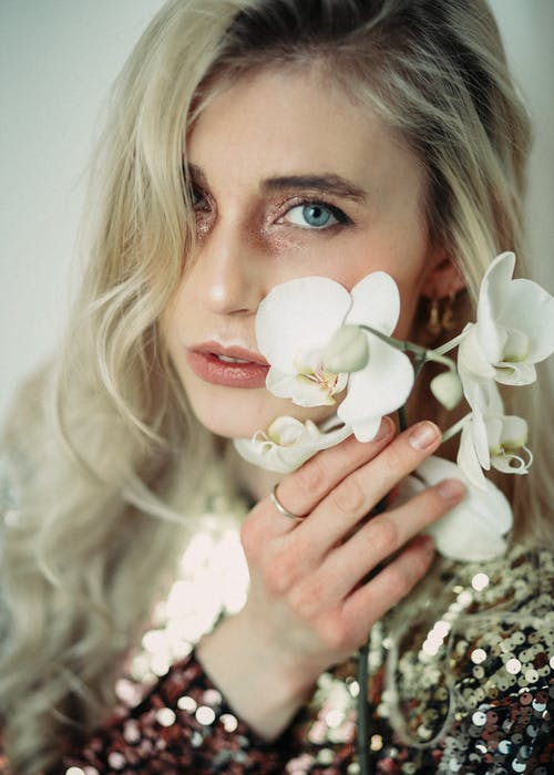 Young woman touching face with blooming orchid