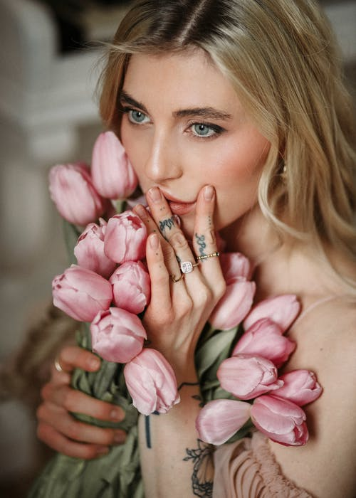 High angle of young female with makeup touching lips and pink blooming tulips and looking away pensively