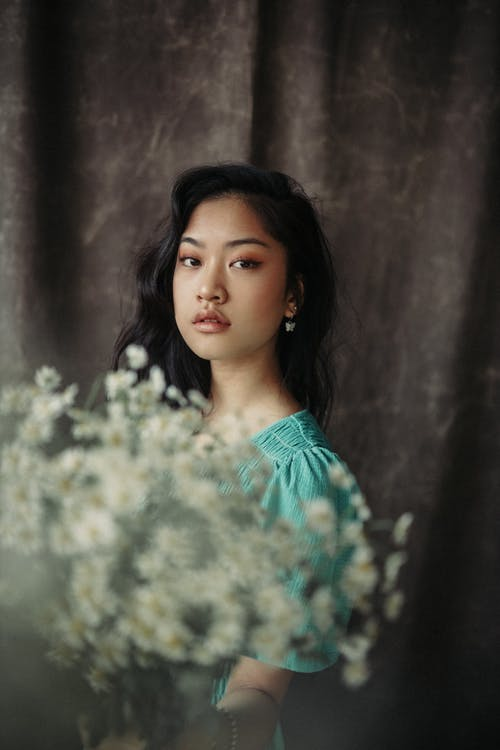 Side view of charming Asian female with makeup and wavy hairstyle wearing dress standing with bouquet of blooming chamomile and looking at camera