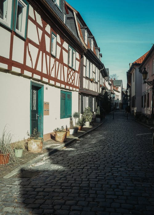 Empty cobblestone street between dwelling buildings located in old town district under cloudless blue sky