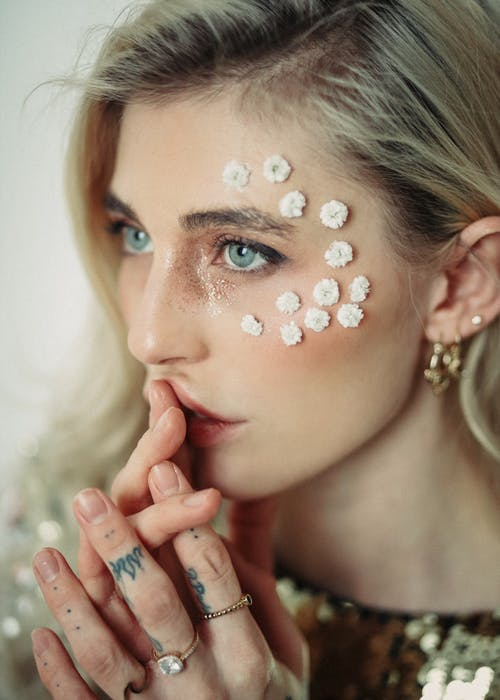 Stylish woman with floral accessories on face