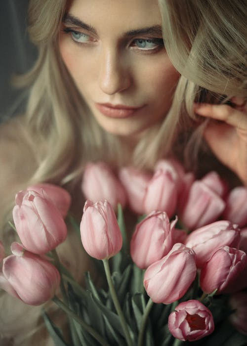 Young woman with bouquet of fresh blooming tulips