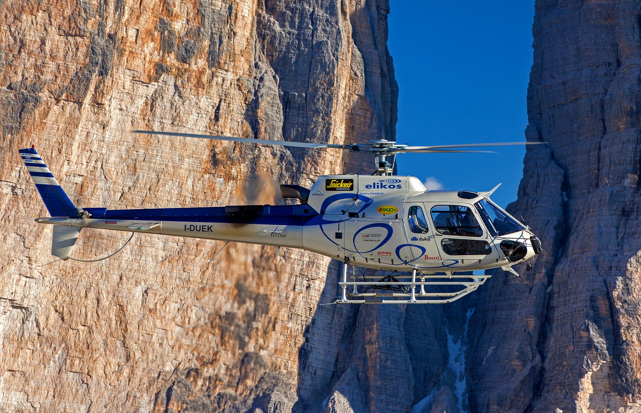 Selective Photograph of White Helicopter Near Brown Mountains