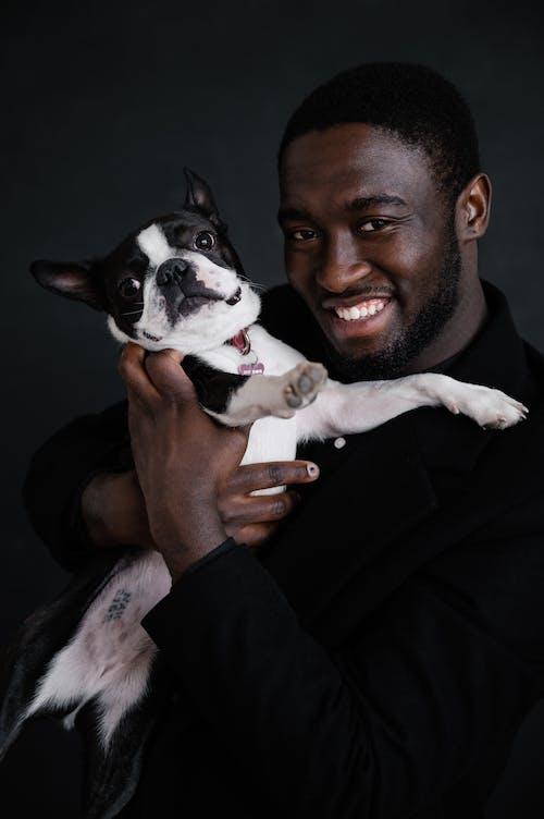 Black man hugging cute dog